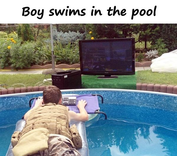 Boy swims in the pool